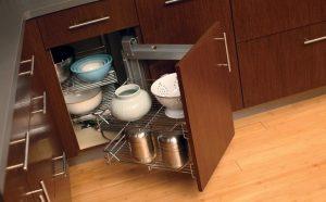 کابینت گوشه: از کنج آشپزخانهی خود به بهترین شکل استفاده کنید در گذشته فضاهای پرت و کنج آشپزخانه بلااستفاده باقی میماندند اما این روزها به کمک تجهیزات جدید از جمله کابینت گوشه میتوان به صورت بهینه از آنها استفاده کرد. در حقیقت، یکی از دغدغههای زندگی آپارتمان نشینی فضای کم آشپزخانه و محدودیت در خرید لوازم آشپزخانه است. همهی ما دوست داریم انواع لوازم آشپزی مانند ساندویچ ساز، سرویسهای تفلون، قابلمه و ظروف چینی خود را به بهترین شکل در قفسهها جای دهیم اما تا همین چند وقت پیش، فضای کوچک آشپزخانه و تعداد کم کابینتها این اجازه را به ما نمیداد. در حال حاضر، کابینت گوشه این مشکل را کاملا حل کرده است. تنها کاری که طراحان انجام میدهند پر کردن فضاهای پرت و خالی با کابینتهای مناسب است. این کابینتها طرحهای متنوعی دارند و دغدغهی شما را درباره کمبود فضا در آشپزخانه رفع میکنند. در ادامه به نکات مهمی درباره راهنمای خرید این کابینتها و معرفی انواع آن خواهیم پرداخت. به این نکات در خرید کابینت گوشه توجه کنید فضای مورد نظرتان را اندازه گیری کنید کابینتهای کنج میتوانند به شما کمک کنند تا از فضای محدود آشپزخانه حداکثر استفاده را بکنید اما قبل از هر اقدامی باید بررسی کنید که آیا اندازهی گوشهی آشپزخانه شما برای نصب این نوع کابینتها مناسب است؟ شما باید به خوبی فضا را بررسی کرده و با توجه به آن برای نصب یا سفارش کابینت گوشه اقدام کنید. تعیین تعداد کابینتها با توجه به فضایی که در اختیار دارید نیز به شما کمک میکند تا با توجه به بودجهتان کابینتهای مورد نیاز خود را بخرید. مدلهای کابینت گوشه را مطابق با دکوراسیون آشپزخانه انتخاب کنید از آنجایی که کابینت گوشه در مدلها و رنگهای مختلفی وجود دارد، ممکن است با دیدن تنوع این کابینتها دچار سردرگمی شوید. یکی از فاکتورهایی که به شما در انتخاب درست کمک میکند، رنگ و دکوراسیون آشپزخانهی شما است. اگر فضای آشپزخانه شما مدرن است، نباید کابینت گوشه با طرح و نقش کلاسیک انتخاب کنید. همچنین رنگهایی که با رنگ فضا و کابینتهای آشپزخانه هماهنگی ندارند، مناسب نیستند. بنابراین حتما باید به دکوراسیون آشپزخانه خود توجه کنید. کاربرد کابینت خود را بررسی کنید تصمیم بگیرید که به چه منظوری میخواهید از کابینت گوشه استفاده کنید. طراحی داخلی کابینتهای گوشه برای قابلمه یا لیوانها و فنج